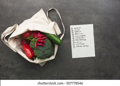 Cotton shopping bag full of vegetables and fruits with checked shopping list. Flat lay food on table.