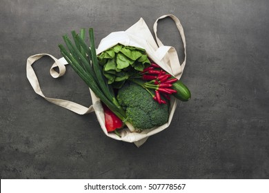 Cotton shopping bag full of vegetables and fruits. Flat lay food on table.