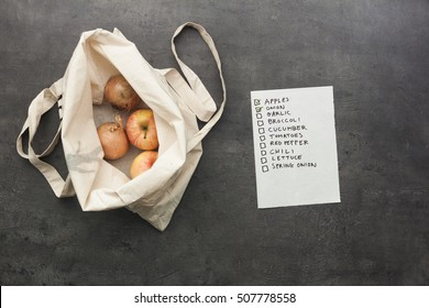 Cotton shopping bag with onion and apples inside with checked shopping list. Flat lay food on table.