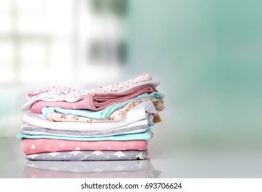 Cotton stack of pastel colorful folded clothes  empty space background.Household concept.Clean laundry pile.Baby apparel.