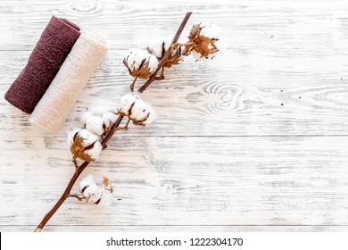 Cotton towels high quality. Set of towels twisted coil near dry cotton flowers on white wooden background top view space for text
