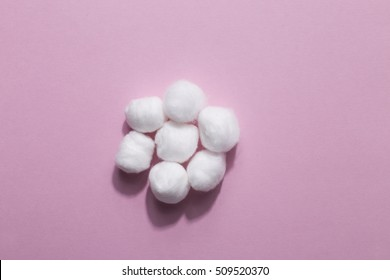 Cotton wool balls on pink background. Extra fluffy swabs