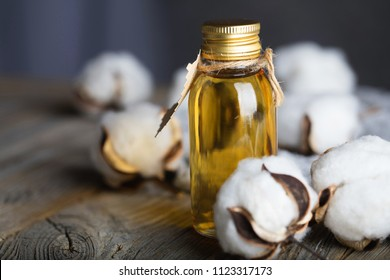 Cottonseed oil in a glass bottle on a wooden surface. Closeup