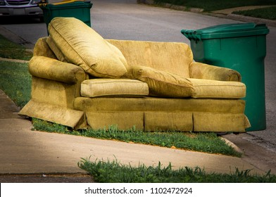 Couch placed by curbside next to garbage can on bulk trash pickup day.