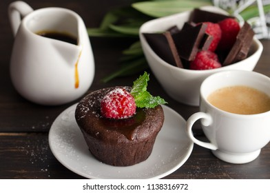 Coulant or Chocolate fondant with raspberry, mint  and powdered sugar. Delicious french dessert and cup of coffee