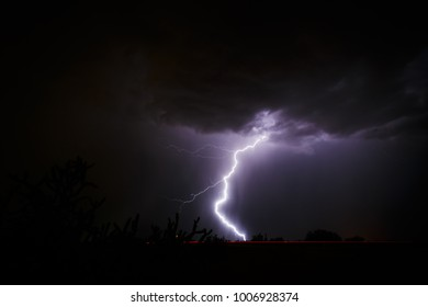 Could to ground lightning bolt with black cloud. Arizona monsoon. Stormy Sky background.