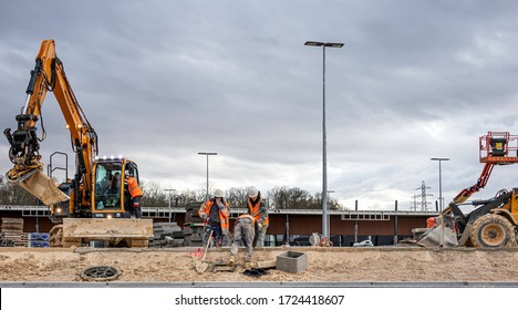 COULOMMIERS, FRANCE - DECEMBER 17, 2019. Site for construction of a car park. Two yellow backhoes in action, and three workers are working to align the curbs of the cement sidewalks.
