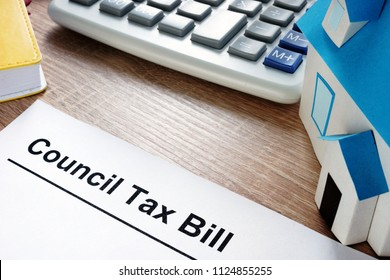 Council Tax Bill and model of house on a desk.