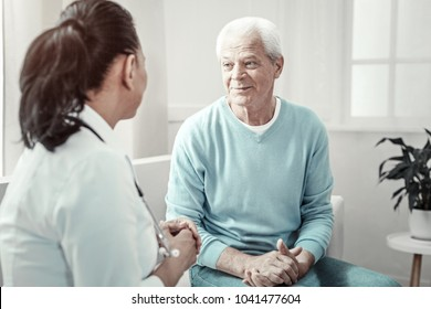 Counseling day. Old grey pleasant man sitting in the room on the sofa speaking with a doctor and holding hands on his knees.