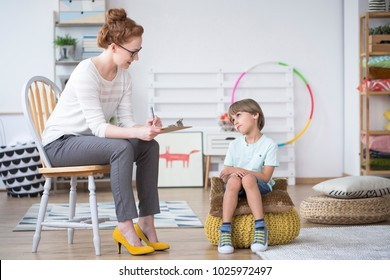 Counselor analyzing the behavior of a young, autistic boy in the classroom
