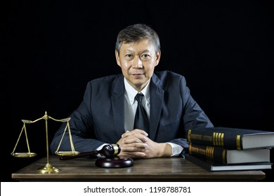 Counselor or Male lawyer working on courtroom sitting at the table. Legal law, Judge gavel with Justice lawyers advice with gavel and Scales of justice.