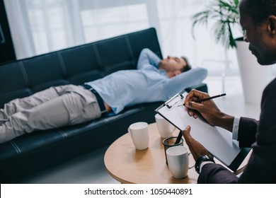 Counselor writing in clipboard and young male patient laying on sofa