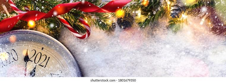 Countdown bis Mitternacht. Retro-Uhr, die letzte Augenblicke vor Weihnachten oder Neujahr 2021 neben dekorierten Tannenbaum zählt. Von oben anzeigen.