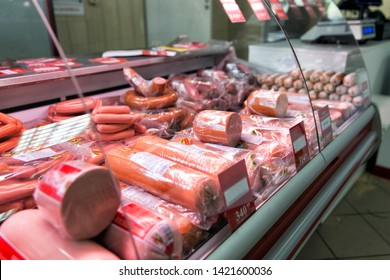 Counter with boiled sausage in store. Refrigerator shelves with different meat products