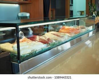 Counter Japanese sushi bar contain fresh raw fish such as salmon, tuna, hamachi  and kani in glass window refrigerator.