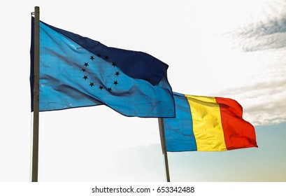 Counter light photo of EU and Romanian national flag waving on wind