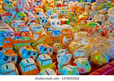The counter of the street stall of Warorot Night Market is full of ceramic souvenirs, small figurines, dolls and piggy banks, Chiang Mai, Thailand