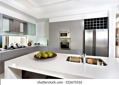 Counter top made in ceramic seen closely with fruits on a brown color clay dish next to the modern  silver faucet attached to the sink, the silver refrigerator .