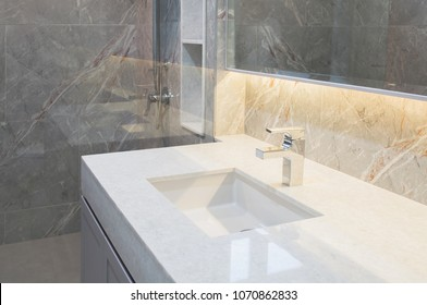 Counter top white marble with washbasin.Wall and floor beige,grey marble stone interior design of restroom or toilet background.Restroom clean design with accessories  background.