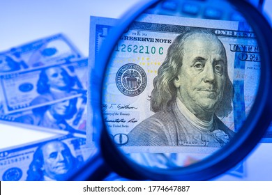 Counterfeit money. A hundred-dollar bill is studied with a magnifying glass. Money in the ultraviolet light. Concept - checking dollars for authenticity. Search for watermarks on banknotes. Fake
