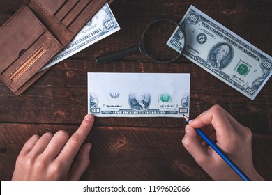 Counterfeiter forges banknotes. Fake concept. Fake money, a wallet with American dollars, a magnifier on a wooden background. Top view