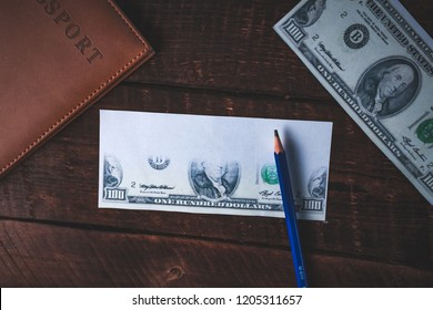 Counterfeiter forges banknotes. Fake concept. Fake money, American 100 dollars, a passport on a wooden background