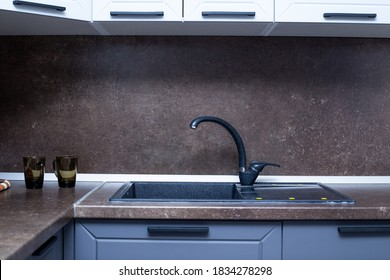 countertop with built-in sink made of black artificial stone, kitchen interior.