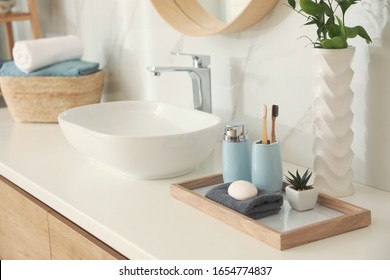 Countertop with sink and toiletries in bathroom. Interior design