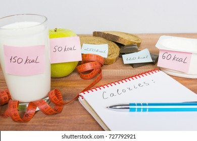 Counting calories, different food with written quantity of calories, diet concept.
