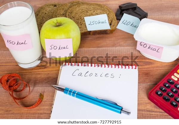 Počítání kalorií, různé potraviny s písemným množstvím kalorií, koncept stravy.
