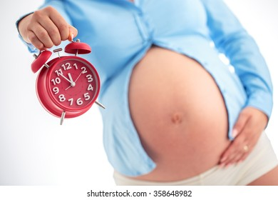 Counting hours expecting child birth. Motherhood concept. Pregnant woman holding alarm clock, studio shot.
