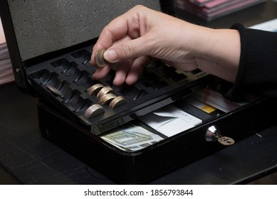 counting the money in the petty cash, coins and banknotes