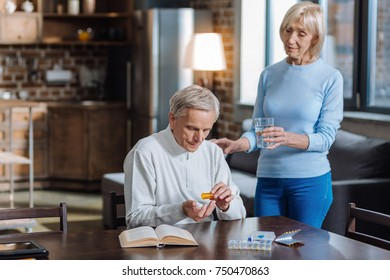Counting pills. Serious concentrated aged man being very attentive while sitting at the table and counting pills with his aged wife standing by his side