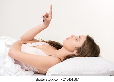 Counting sheep. Young beauty lying in bed and pointing at copy space on white background