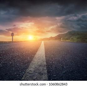 Country asphalt road at sunset