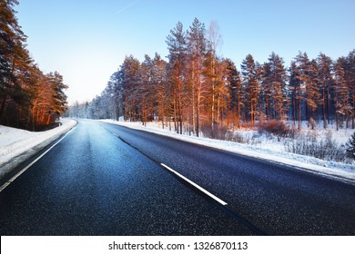 A country asphalt road through the snow-covered forest on a clear sunny day. Lapland