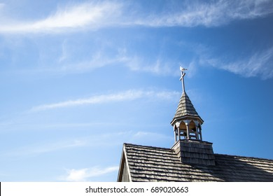 Country Church Steeple And Blue Sky. Small rural wooden church steeple with an old wooden cross at the top