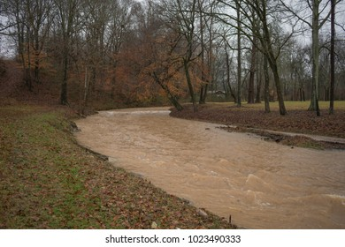 Country Creek Swollen from Floodwaters, Brown with Washed Away Topsoil, Bursting from it's Banks Flowing North to South