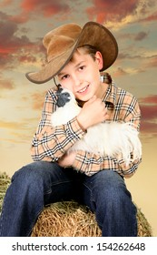 A country farm boy sitting on a lucerne bale and holding a bantam chicken at sunset