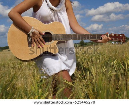 Country girl sitting with guitar at wheat field
