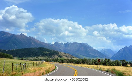 Country highway curves toward the beautiful Absaroka Mountains in Happy Valley, Montana.