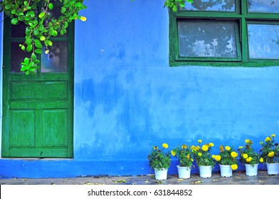 Country house with blue colored wall, green door and window and yellow flowers in pots. Colorful abstract background