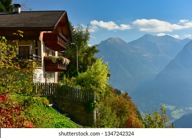 Country house built on a mountainside overlooking the Alps on a sunny autumn day. Alpine village Stulles, municipality of Moos in Passeier, South Tyrol, Italy. - Shutterstock ID 1347242324