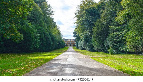 a country house driveway with the house in the distance