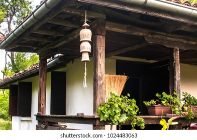 Country house facade with ceramic clay pottery decorative garden wind chime bells on a rope under wooden beams rustic house roof