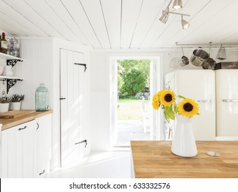 country house kitchen interior with sunflowers in a vase and a open door out to the garden