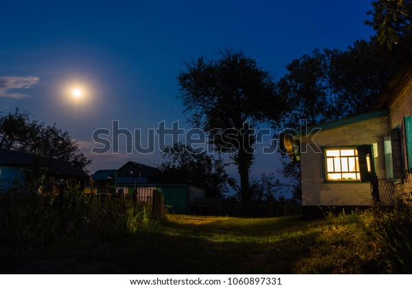 Country house yard in a summer moon night. Moon in a night sky.