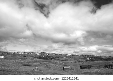 Country landscape with farmhouses under cloudy sky in Torshavn, Denmark. Beautiful landscape view. Hilly terrain with green grass. Overcast sky. Nature and environment. Summer vacation in countryside.