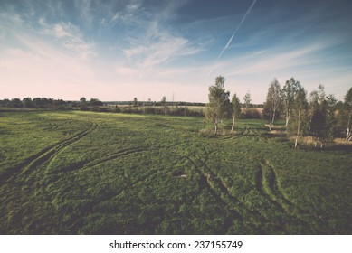 country landscape with fields and blue sky with plane trails - retro, vintage style look