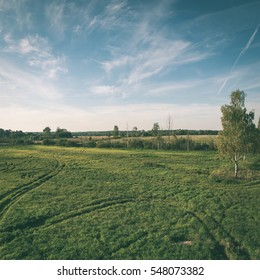 country landscape with fields and blue sky with plane trails - instant vintage square photo